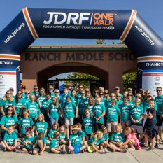 Group of kids and adults wearing the same blue walk for diabetes shirt in a group photo in front of Ranch Middle School