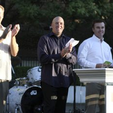 Three men on stage in in front of a drum set and behind a podium, clapping hands